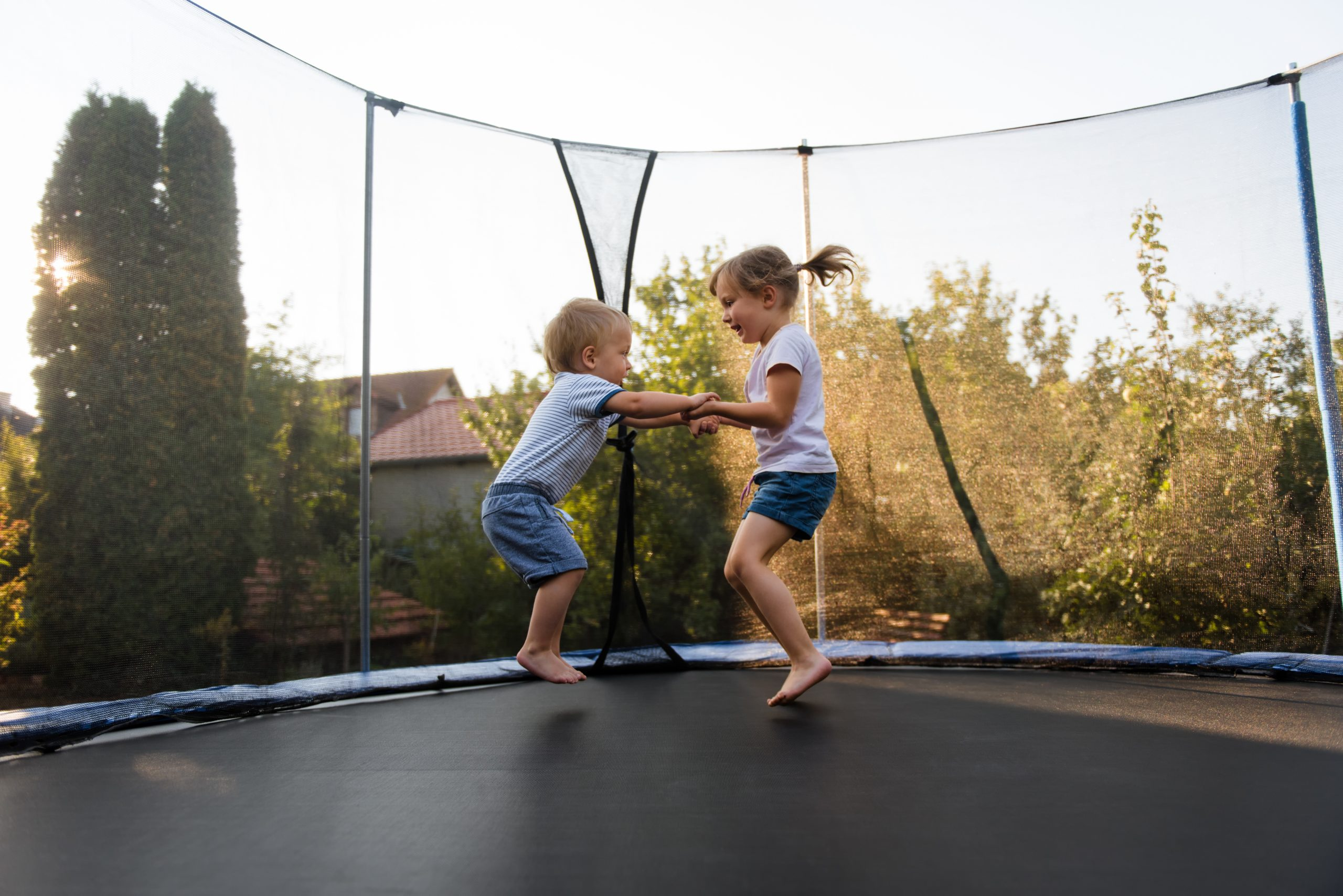 Boy and girl on a trampoline holding hands and bouncing